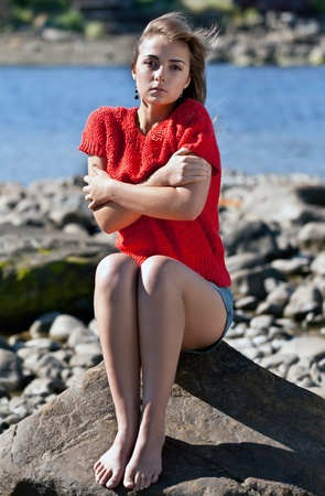 trembling: girl badly frozen sitting on a rock in a red sweater against the rocky shore of the White Sea