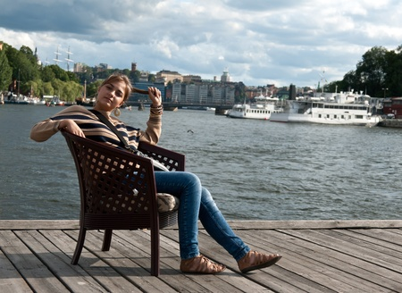 beautiful girl sitting in a chair on the pier