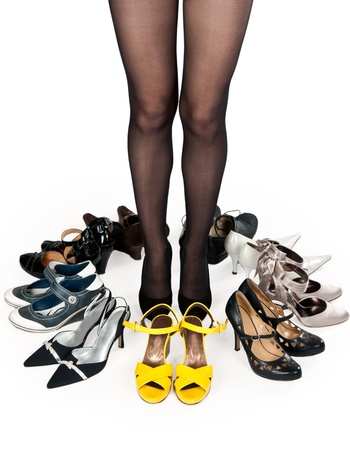 shoe store: female legs in pantyhose, surrounded by stylish shoes in the studio on a white background