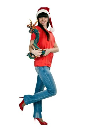 Girl in Santa hat with a decorative wooden dragon in studio isolated on a white background photo