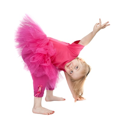 little girl in a pink dress dancing in the studio bow isolated on white background photo