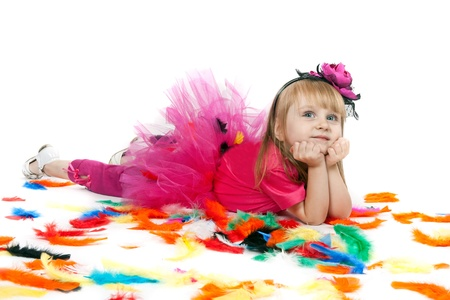little girl lies on a white background color throws feathers photo