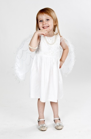 little girl with wings on a gray background photo