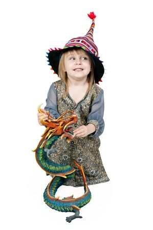 Little girl sitting on the floor with a decorative dragon in the studio on a white background   photo