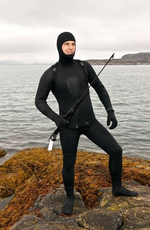 Freediver in a diving suit on the Barents Sea with an underwater pneumatic gun