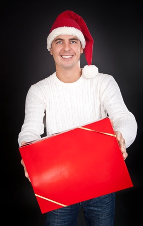 Smiling man in Santa hat gives a red box in the studio against a dark background photo
