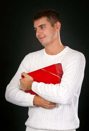 sad man with a red gift box in a studio against a dark background photo