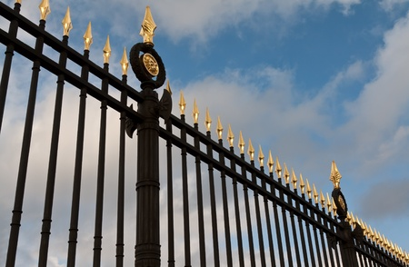 steel fence with gold spears against the sky photo