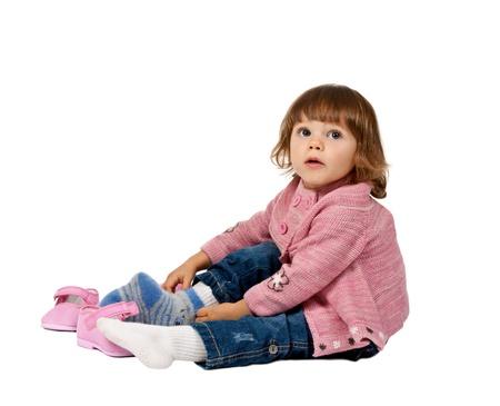 pied jeune fille: petite fille porte des chaussures sur un plancher blanc dans le studio