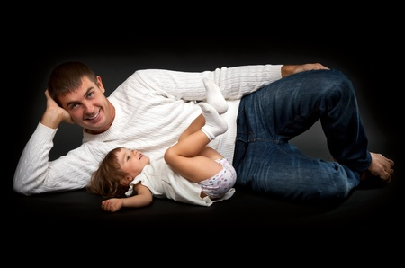 happy father with his little daughter lying on a black background