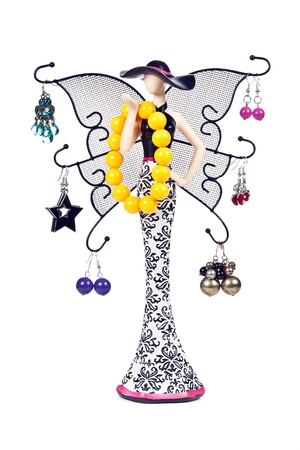 statuette woman with wings hung with jeweled earrings and a bracelet photo