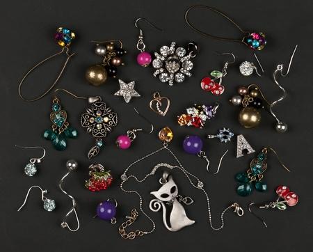 jewelery, earrings scattered on a black background photo
