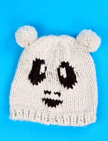 knitten: knitted wool hat with a pattern of little faces on a blue background