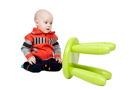 child dropped a plastic chair in the studio on a white background photo