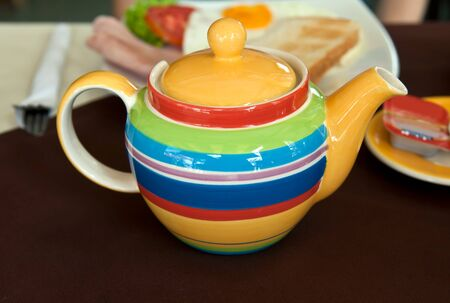 colored striped teapot on the table with breakfast photo