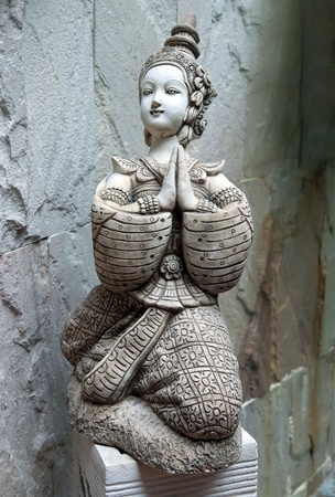 Asian statue in the form of a girl praying photo