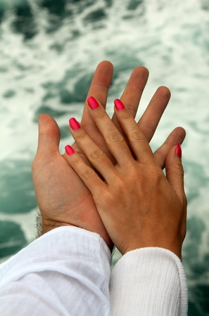 Mens and Womens tanned hands against the sea Stock Photo