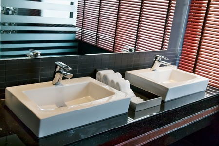 two square sink in the bathroom with a window and shutters