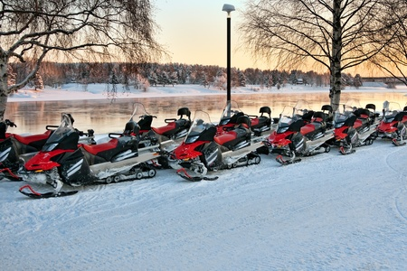 Vehicles are a number of snowmobiles in the parking lot photo
