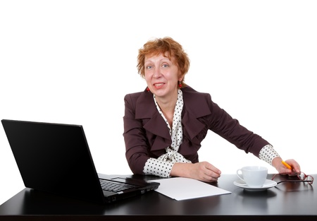 Middle-aged woman at the table, a laptop in the studio on a white background photo