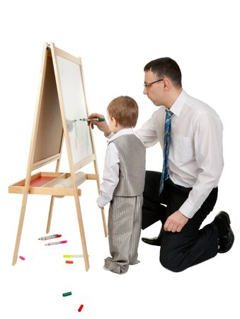 teaches: Businessman teaches his son to paint on an easel, isolate on white Stock Photo