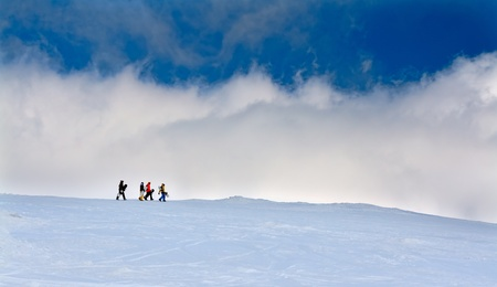 Four snowboarders go up the hill against the sky photo