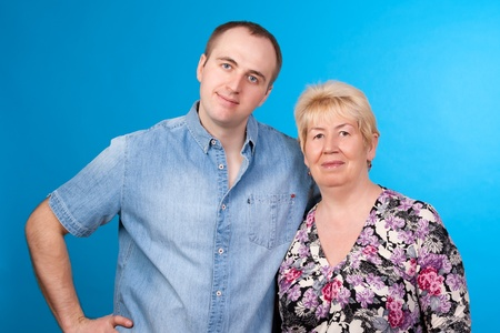 portrait of mother and son in a studio on blue background Stock Photo - 13246470