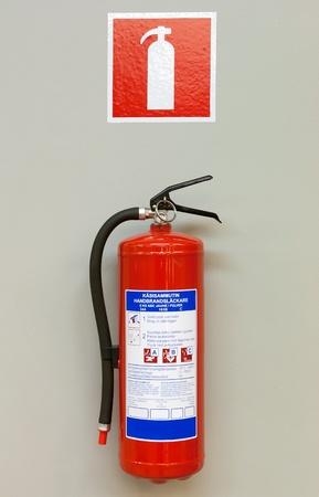 seguridad industrial: Extintor de incendios en la pared gris