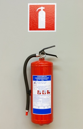 Fire extinguisher on the gray wall photo