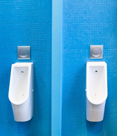 flushing: Modern urinals on the blue tiled wall