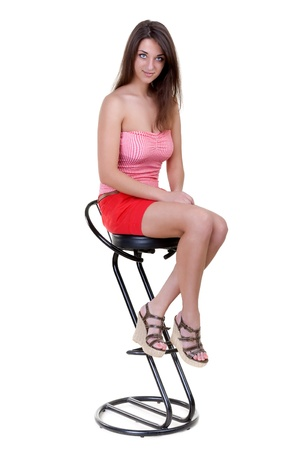 Portrait of a beautiful girl sits on the bar stool isolate on a white background