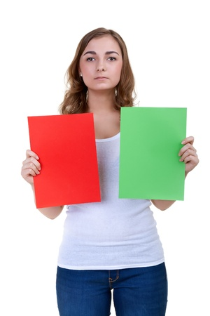 18's: A serious girl shows green and red desert sheets of paper on a white background Stock Photo