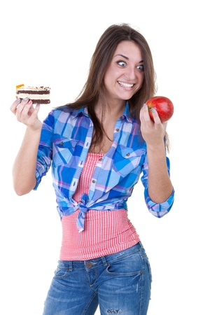 eagerly: The girl eagerly looking at the apple and holding a cake. Isolate on white