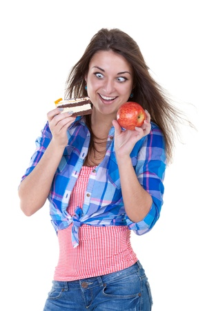 eagerly: The girl eagerly looking at an apple and a cake in the throes of choosing Stock Photo