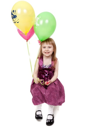 A laughing kid in red dress is playing with balloons; isolated on the white background photo