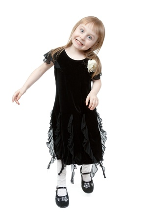 The little girl in a black suede dress hamming in the studio on a white background photo