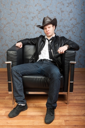 Brutal man in a cowboy hat sitting in leather chair in a luxurious interior photo
