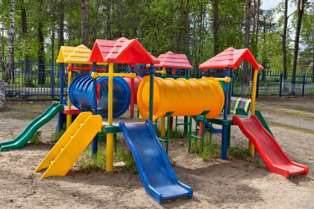 Plastic multi-colored children's playground in a pine park on a sunny day Stock Photo - 14316950