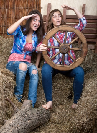 cute young farm girl: Two beautiful girls in the hay with a wheel on the cart are looking into the distance Stock Photo