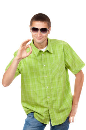ok symbol: Smiling young man with sunglasses wearing checkered shirt shows Ok symbol. Isolated on white background, mask included