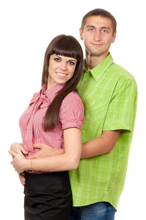 A man in a green plaid shirt hugs a beautiful brunette girl in a red plaid shirt. Family portrait on a white background. photo