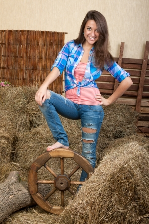 Girl with a wheel on the wagon for hay in the rural interior photo