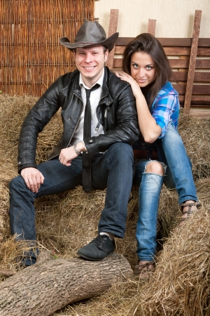 A young cowboy with sexual girl sitting on the hay photo