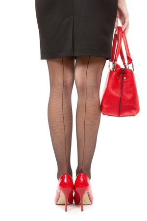 Beautiful female legs with red high heels holding shopping bags isolated on white background, business money spending concept photo