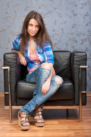 Portrait of beautiful brunette girl in a plaid shirt, sitting in leather chair against the wall with a retro pattern photo