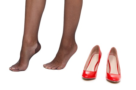 Beautiful female feet and near a pair of red high-heeled shoes. Isolate on white. Stock Photo - 14494477