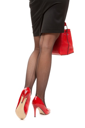 Leisure bag. A close-up of a chic red handbag along with sexy female legs wearing elegant red shoes. photo