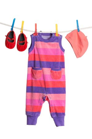A set of childrens clothes hanging on a clothesline. Isolate on white. photo