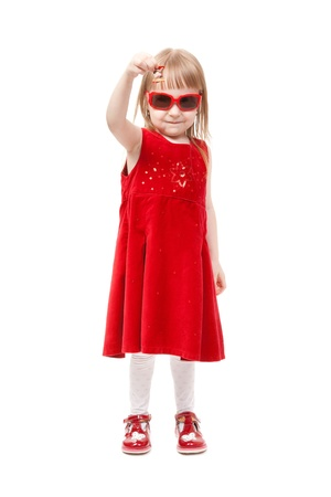 Charming girl in red dress and sunglasses show delicious candy. In the studio, isolated on white background photo