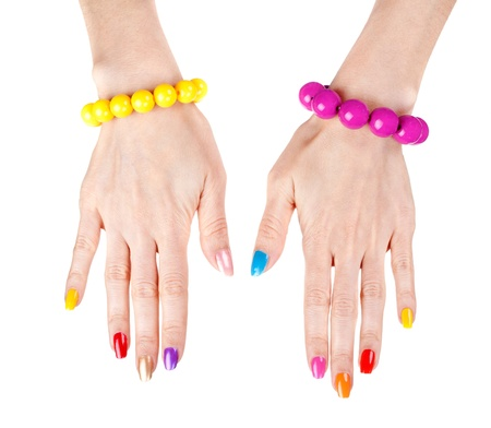 manicure woman: Womens hands with a fashionable multi-colored nail polish with the bracelets. Studio, isolate on white. Stock Photo